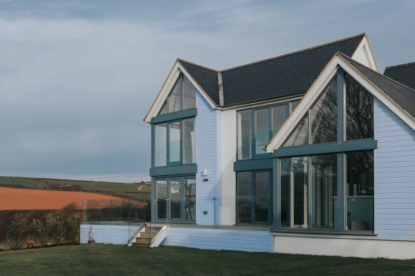 Timber clad beach house with large windows by South Devon Architects Andrew Lethbridge Associates