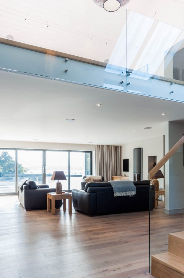 open plan living space with frameless glass balustrade by South Devon Architects Andrew Lethbridge Associates