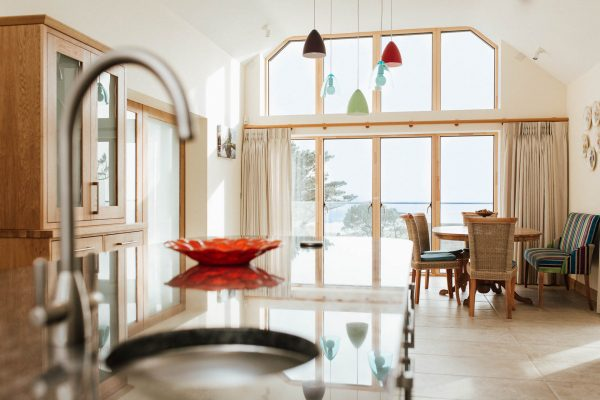 open plan kitchen dining space with a large glazed wall in a new thurlestone beach house by south devon architects andrew lethbridge associates