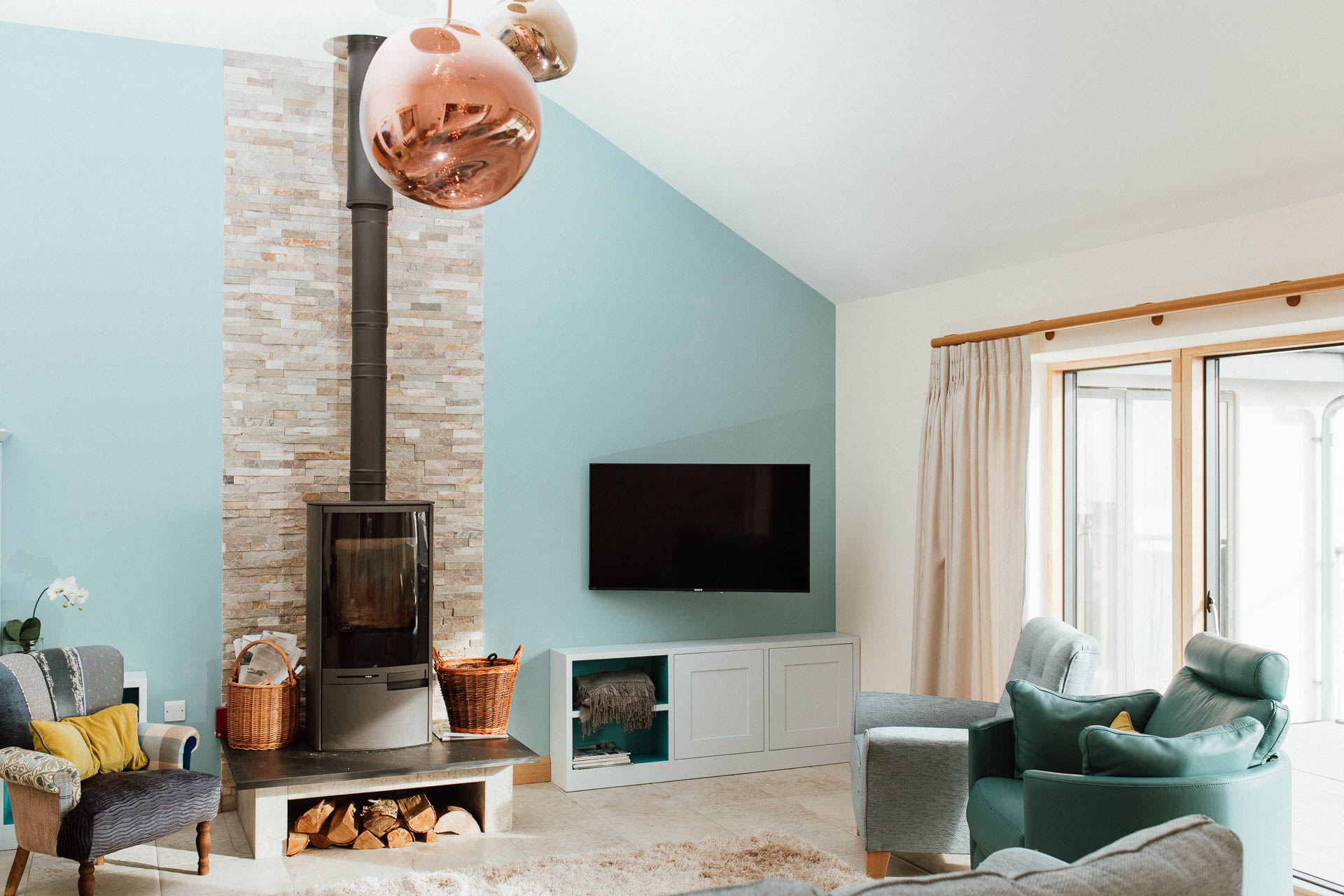Stove and log store in a new thurlestone home by south devon architects andrew lethbridge associates