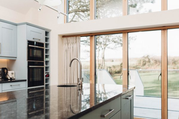 kitchen island with views to the garden through ideal combi sliding doors by south devon architects andrew lethbridge associates