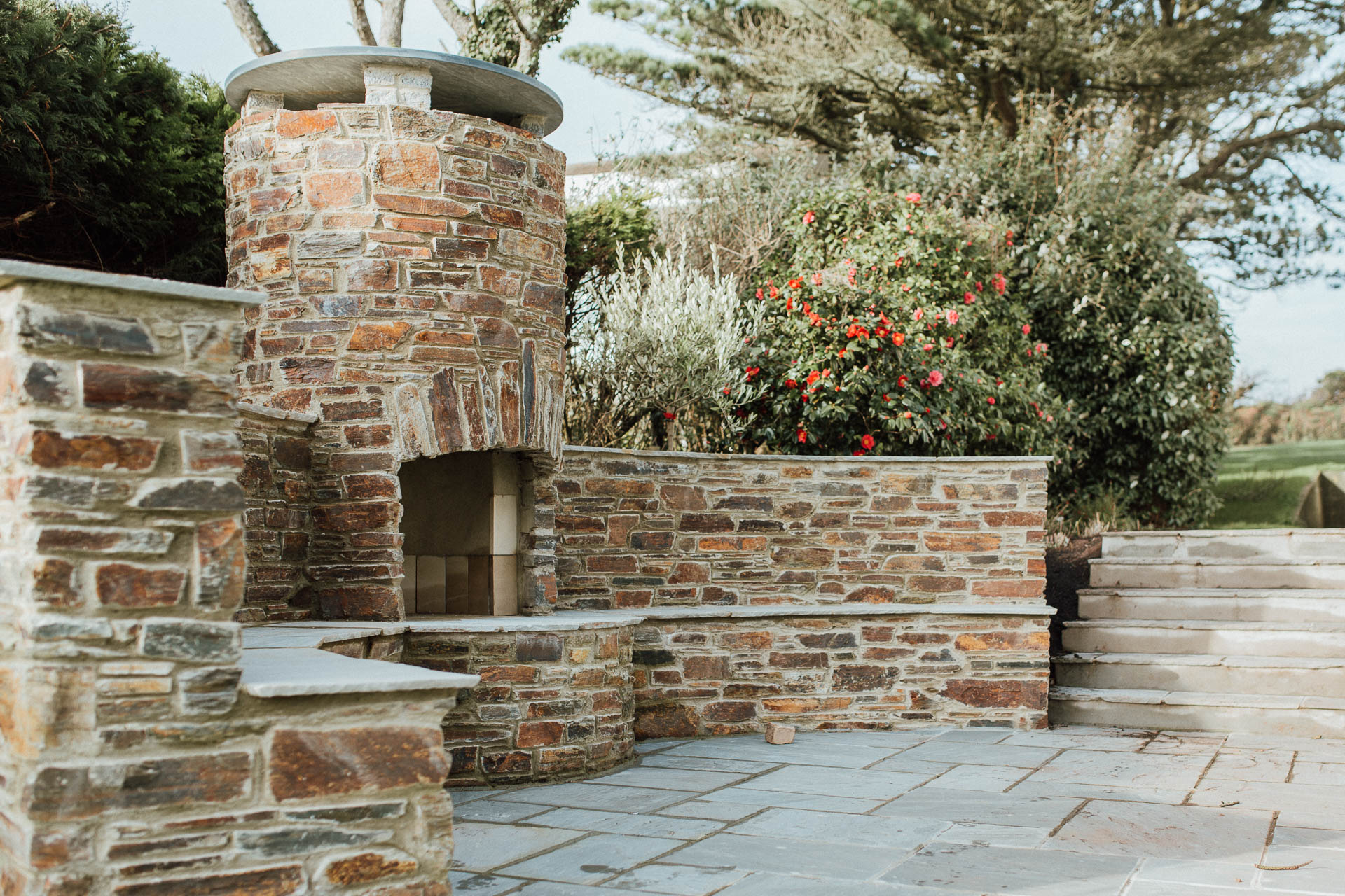 bespoke natural stone bbq and outdoor seating area in the garden of a new family home in thurlestone by devon architects andrew lethbridge associates
