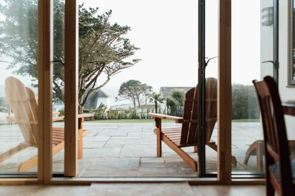 view of the sea through ideal combi sliding doors installed in a new thurlestone house by south devon architects andrew lethbridge associates