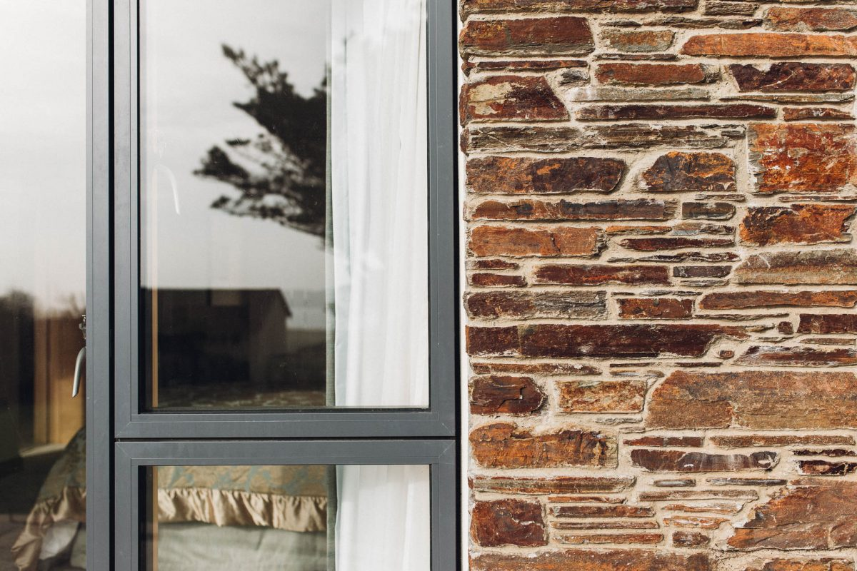 idealcombi windows in a stone clad wall of an award winning house by south devon architects andrew lethbridge associates