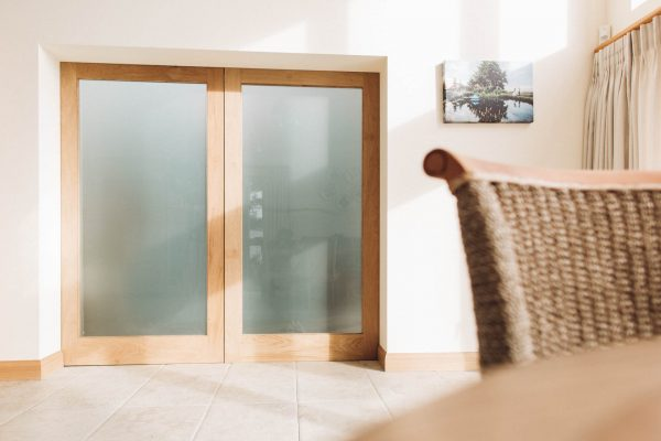 oak sliding pocket door with opaque glass to the living room in a new thurlestone beach house by devon architects andrew lethbridge associates